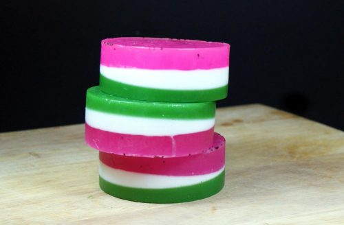 This easy watermelon soap recipe is perfect for summer and incorporates not only a fun watermelon color theme, but also shimmering cosmetic glitter! They'd look great by any sink or you could also craft a smaller version to gift these as DIY summer party favors.