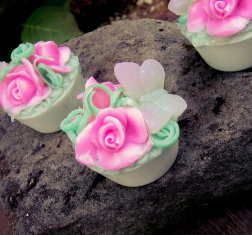 Garden Butterfly Soap Wedding Favors from LolliLuscious. These artisan soaps are delicately created with perfectly pink rose buds nestled in green grass with a soft pink butterfly. They are available packaged in either a party-ready cello bag or pretty gift box.