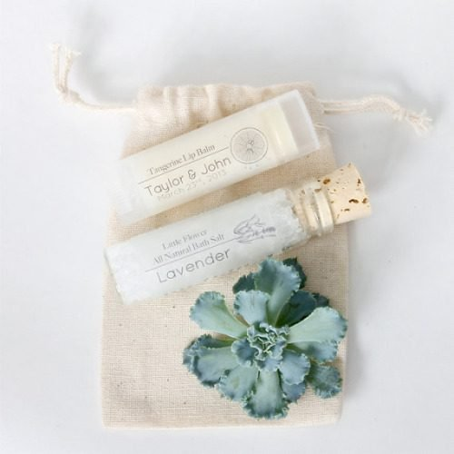 These cute bath salt and lip balm wedding favors from Little Flower Soap Co. come tucked into a natural muslin drawstring pouch.