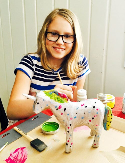 Hannah painting a paper mache unicorn with materials from Target!
