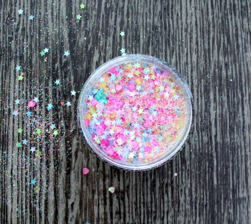 Learn how to make your own DIY unicorn body glitter to wear to summer festivals and parties! Probably one of the easiest things you'll make this year, this super sparkly unicorn body glitter is made with a combination of iridescent fine rainbow colored glitter and heart and star spangles.