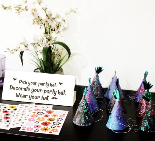 Pick your own party hat station and a DIY Unicorn Party Hat Hack! These mini pineapple party hats were transformed to dreamy unicorn colors with spray paint and glitter!