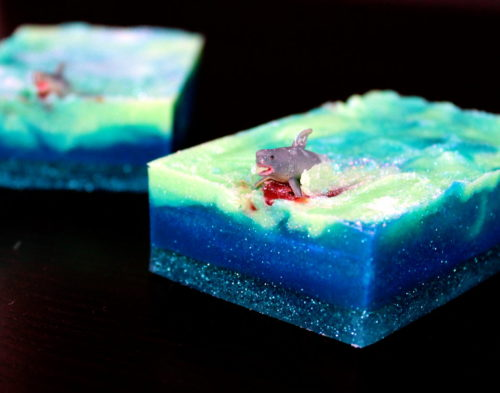 Shark Attack Soap Recipe! Celebrate sharks with this super fun shark week soap DIY! Whether you're celebrating shark week or want a bloody fabulous Halloween gift, these melt and pour soaps are sure to add some excitement to anyone's bath. Not only are they easy to make, but they also make great gifts as well as party favors for say, a shark themed birthday or pool party. (Sense of humor required, of course.)