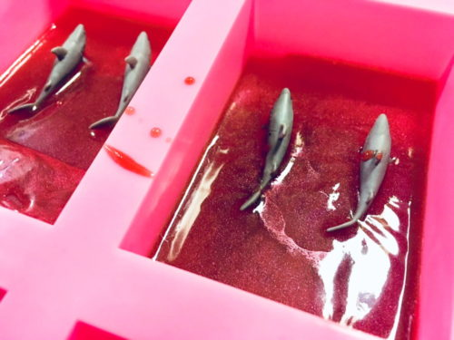 Shark Attack Soap Recipe! Celebrate sharks with this super fun shark attack soap DIY! Whether you're celebrating shark week or want a bloody fabulous Halloween gift, these melt and pour soaps are sure to add some excitement to anyone's bath. Not only are they easy to make, but they also make great gifts as well as party favors for say, a shark themed birthday or pool party. (Sense of humor required, of course.)
