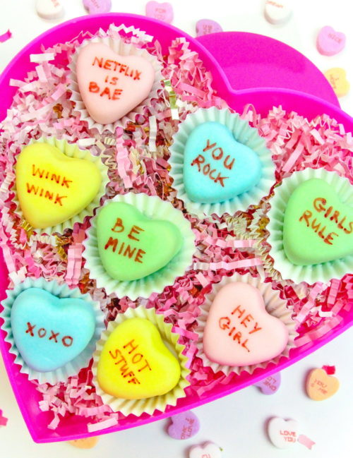 These Conversation Heart Petit Fours via Brite & Bubbly make delicious, edible DIY Valentine's Day gifts for your sweetheart or Galentine! #galentinesday #valentines #valentinesdaygift #conversationhearts #hearts #petitfours #diy