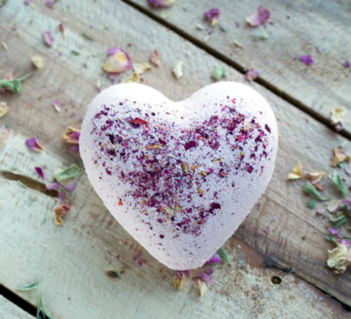 Craft these natural DIY rose milk bath bombs via The Nerdy Farm Wife as DIY Valentine's Day gifts! These beautiful heart-shaped bath bombs are naturally colored with rose clay and scented with a relaxing blend of essential oils, while creamy cocoa butter and milk powder are added for their extra skin-loving benefits. #valentinesdaygift #bathbombs #diy