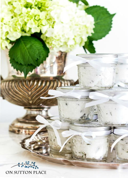 Mason Jar Crafts for Bath & Beauty Lovers! These DIY rosemary sugar scrubs via On Sutton Place are made with a simple skin care recipe that consists of coconut oil, sugar and rosemary and make delightful party, hostess or wedding favors. #masonjarcrafts #diy #favors #skincare #scrubs #coconutoil #rosemary