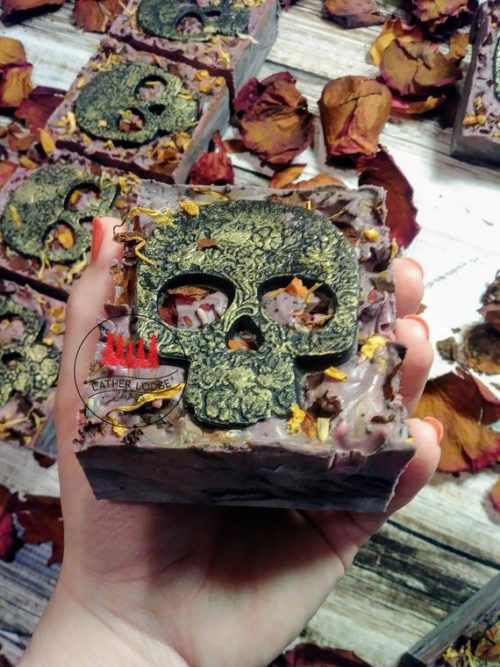 Day of the Dead Soap. This cold process artisan handmade Halloween soap bar from Lather Lodge is bursting with a rich, intoxicating floral fragrance. Reminiscent of the Day of the Dead, the top of this soap is generously embellished with red rose petals, pink rose petals, calendula petals, lavender buds, poppy seed, dried orange peel and an antiqued soap skull. While the inside is swirled with dark purple, black and pink.