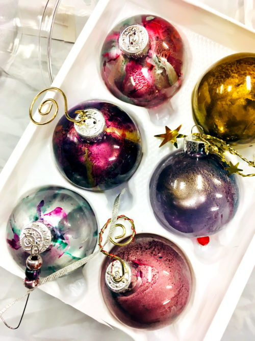 Alcohol ink Christmas ornaments DIY. Learn how to craft beautiful custom alcohol ink ornaments to decorate your Christmas tree for the holiday season. A fun winter activity for kids and families to make together for DIY Christmas decor or handmade Christmas gifts for friends and family. Easy Christmas decor ideas the kids can craft themselves! #kidscrafts #christmasornaments #diychristmasdecor
