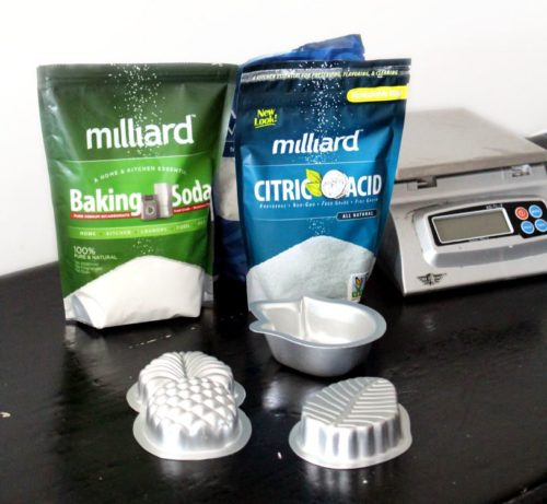 Ingredients for making bath bombs. Baking soda, citric acid, a digital scale and heavy duty bath bomb molds.