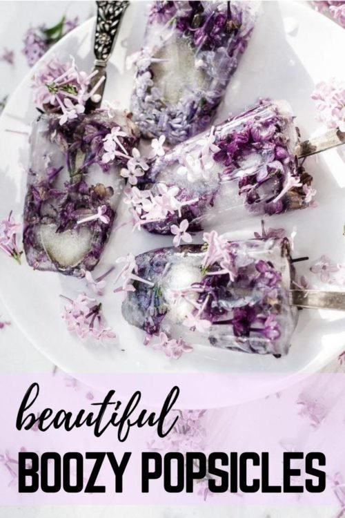 "Beautiful boozy popsicles with edible lilac flowers. Learn how to make ""I'm all grown up"" boozy popsicles with edible lilac flowers with a simple gin and tonic popsicle recipe. It's perfect for spring brunch with your lady friends and a fun way to enjoy a summer treat a season early! You can also use pretty spoons in place of a traditional wooden popsicle stick to make your boozy popsicles the perfect addition to your spring wedding or event."