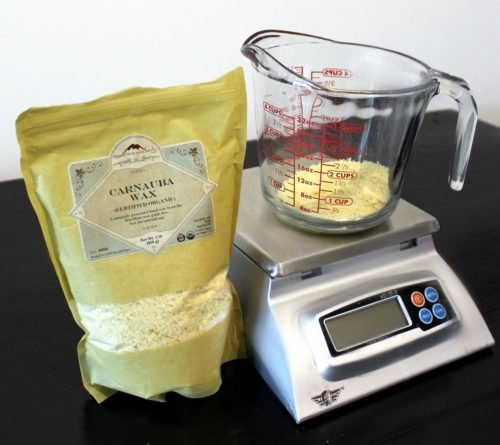 Weighing out carnauba wax to make aloe after sun lotion bars for natural sunburn relief.