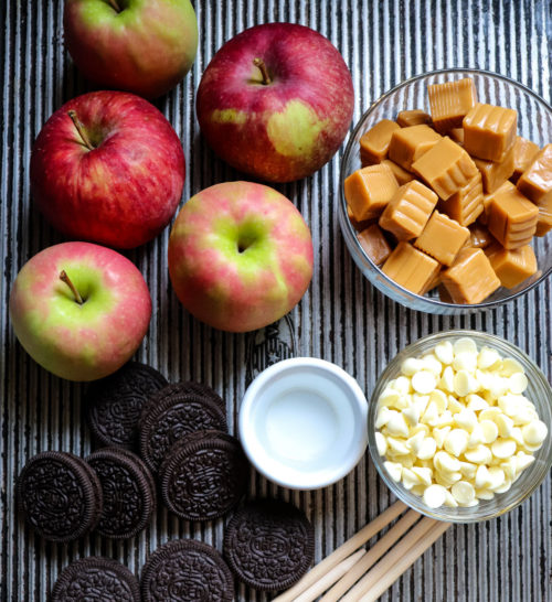 Ingredients for making caramel apples with packaged candy caramels, white chocolate chips and crushed Oreo cookies.