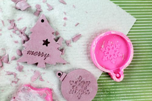 Unmolding plaster Christmas ornaments from silicone ornament shaped molds.