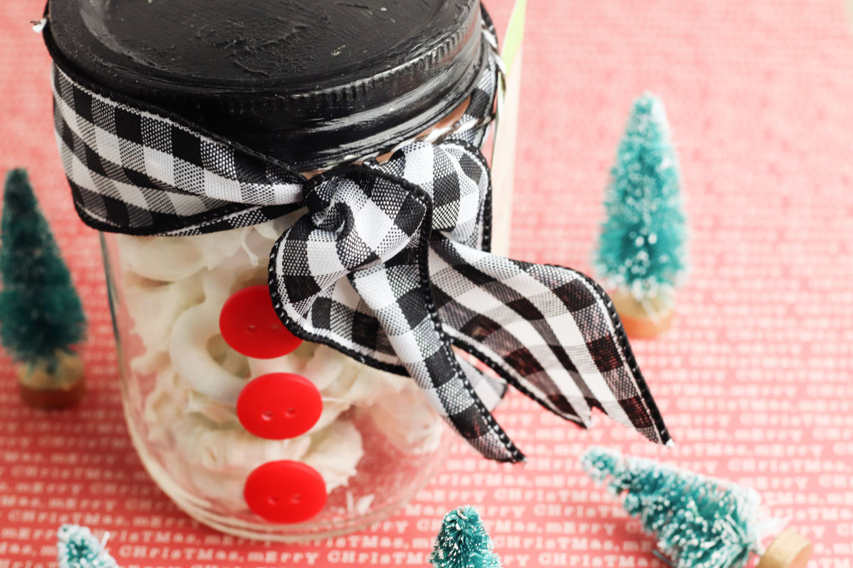 Snowman mason jar gift DIY with free printable Christmas gift tags. If you love snow as much as I do, or maybe you just need a winter craft to keep you from going stir crazy, this snowman mason jar craft is the perfect fit. It's absolutely wonderful for DIY Christmas gifts for teachers, friends, neighbors – pretty much anyone. (I tell you how to make easy white chocolate covered pretzels to stash inside.) Plus, I've also included free printable labels to make gifting even easier.