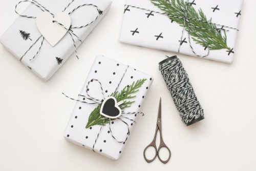 Wrapped handmade Christmas gifts in simple geo black and white holiday wrapping paper tied with bakers twine and topped with an evergreen sprig and a heart shaped Christmas gift tag.