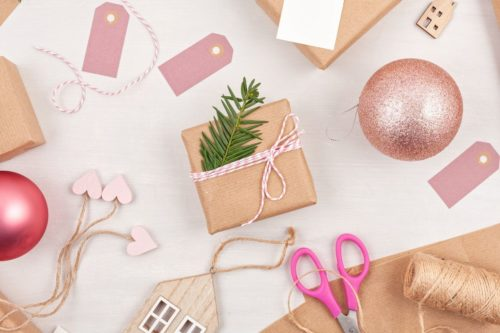 DIY gift wrapping ideas for Christmas using brown paper, evergreens and bakers twine then using Christmas ornaments as gift toppers for holiday gifts.