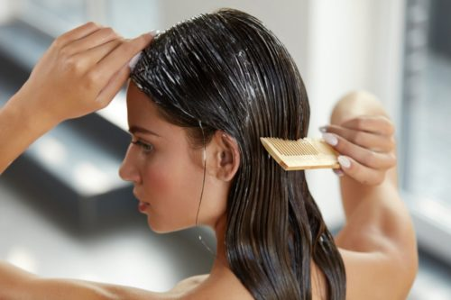 girl combining conditioner through hair after shampooing