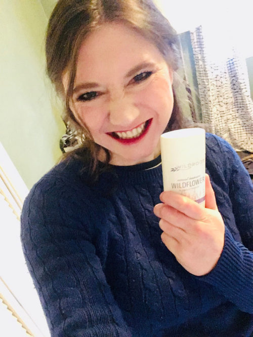 Girl holding natural deodorant from Wildroot in hand.