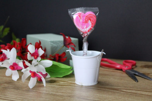 Dollar Tree Valentine Bouquet. Easy DIY Dollar Tree Valentine's Day gifts in 5-minutes or less. I love these little bucket bouquets for Valentine's day. Not only are these Dollar Tree valentines edible, but once the candy is gone the floral arrangement can be used through the month to decorate a small space, sided table or a work desk. And, unlike real flowers, there's not need to swap out the water or worry about them dying. Dollar Store crafts for simple Valentine's Day gifts. #valentines