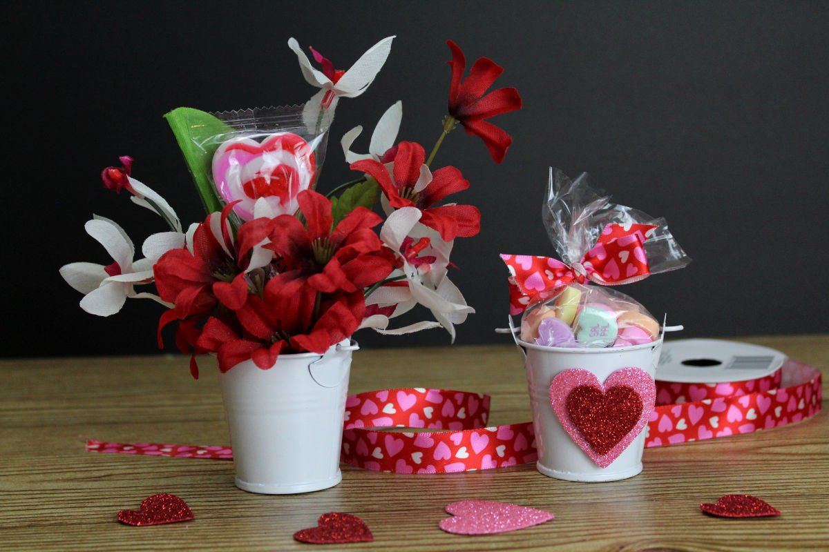 Dollar Tree Valentine's Day Bouquet. Easy DIY Dollar Tree Valentine's Day gifts in 5-minutes or less. I love these little bucket bouquets for Valentine's day. Not only are these Dollar Tree valentines edible, but once the candy is gone the floral arrangement can be used through the month to decorate a small space, sided table or a work desk. And, unlike real flowers, there's not need to swap out the water or worry about them dying.Dollar Store crafts for simple Valentine's Day gifts. #valentine