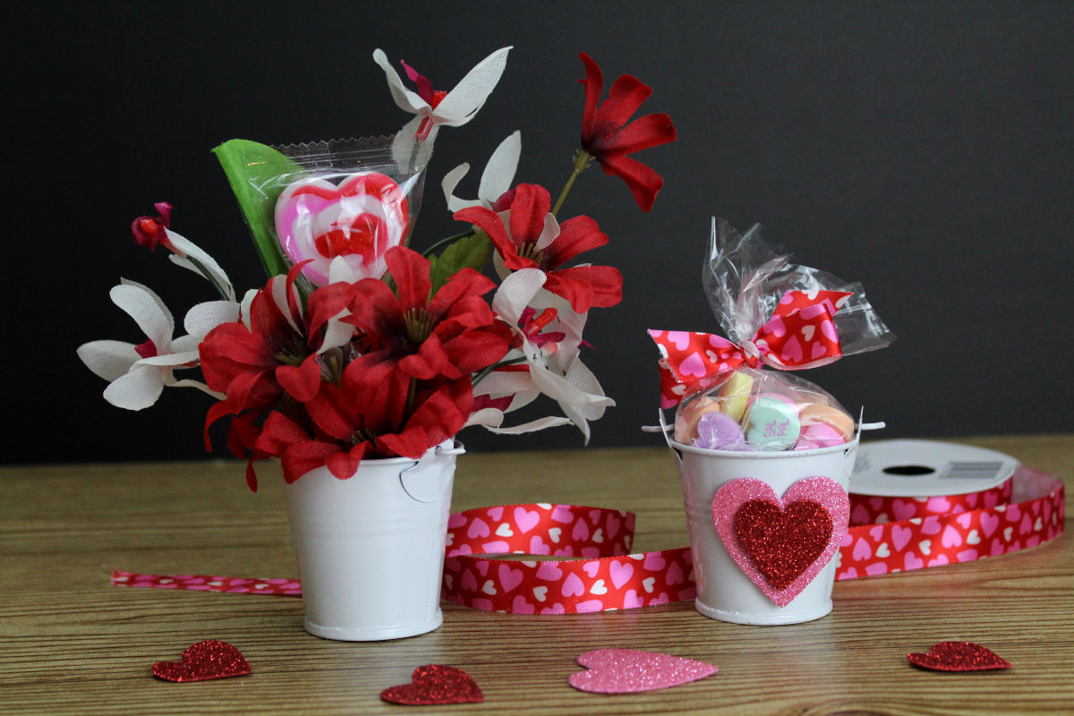 Dollar Tree Valentine's Day Bouquet. Easy DIY Dollar Tree Valentine's Day gifts in 5-minutes or less. I love these little bucket bouquets for Valentine's day. Not only are these Dollar Tree valentines edible, but once the candy is gone the floral arrangement can be used through the month to decorate a small space, sided table or a work desk. And, unlike real flowers, there's not need to swap out the water or worry about them dying. Dollar Store crafts for simple Valentine's Day gifts. #valentine