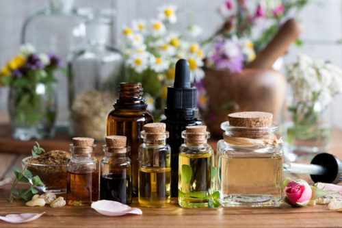 natural essential oil perfumes in glass bottles with flowers and herbs
