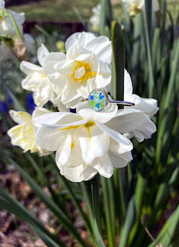 Pressed flower botanical jewelry ring. This handmade ring contains real pressed flowers encased in resin. Update your existing warm weather wardrobe on a budget with customizable botanical resin jewelry from Ann and Joy. These affordable fashion jewelry accessories are made with real flowers preserved in resin. Save money and take the challenge out of shopping for new spring and summer fashions by updating your old outfits with fresh jewelry accessories that stand up to the test of time.