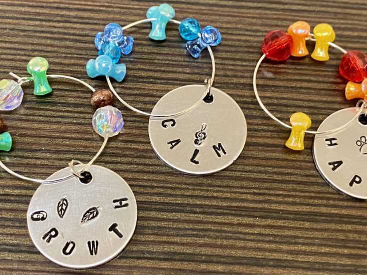 Easy DIY women's crafts. How to make DIY wine glass charms for fun and functional crafts that also make lovely homemade Mother's Day gifts. Pair these DIY wine glass charms with a DIY needle felted wine bag and a bottle of wine for lasting, gift worthy crafts for women. These wine glass charms make beautiful handmade gifts for her and are perfect for DIY Mother's Day gifts. Learn how to use metal stamping on aluminum tags with jewelry elements and beads to make DIY wine glass charms for Mom.