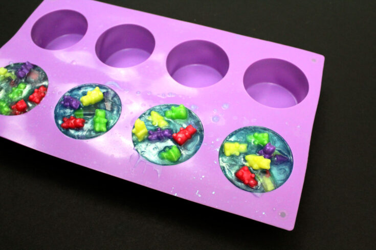 tiny soaps shaped like gummy bears embedded in blue glycerin melt and pour soap base inside a round silicone soap mold