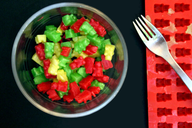 bowl full of yellow, green and red gummy bear soaps beside a silicone gummy bear soap mold with a fork on it